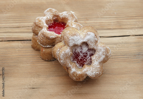 Flowers shape cookies cover with powder sugar on a wooden table