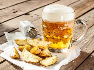 Beer mug and potato wedges on wood table