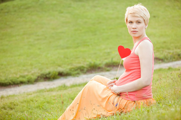 pregnant woman enjoying summer park holding a paper red heart, o