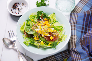 green salad with cucumber, crispy bacon and eggs
