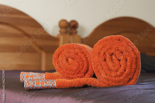 Rolled orange towels on the violet covered bed