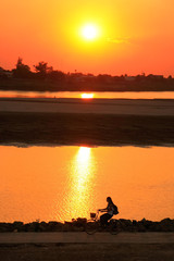 Silhouetted woman riding at Mekong river waterfront at sunset, V