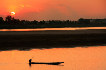 Silhouetted boat on Mekong river at sunset, Vientiane, Laos