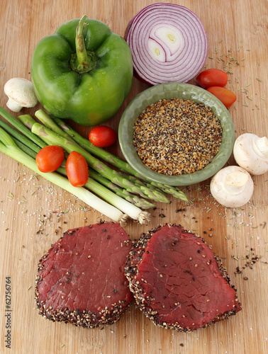 Raw steaks with vegetables and spices