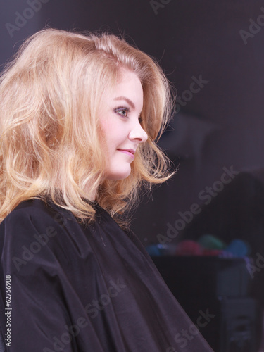 girl with blond wavy hair by hairdresser in beauty salon
