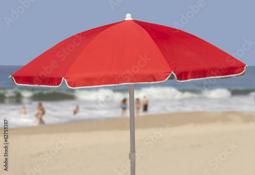 Red beach umbrella in sand by ocean.Blurred people in background
