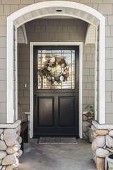 Black front door of a home seen through an arch