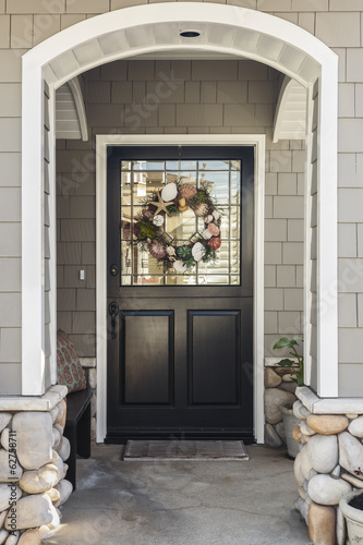 Black front door of a home seen through an arch