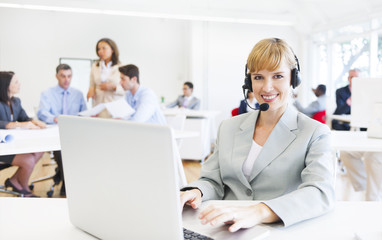 Smiling Call Centre Agent At Busy Office