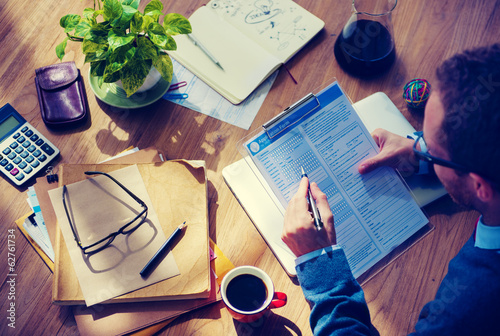 Man Filing Out Application Form At Wooden Table