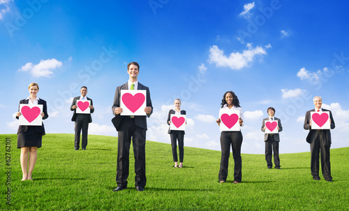 Business PeopleHolding Hearts On a Hill