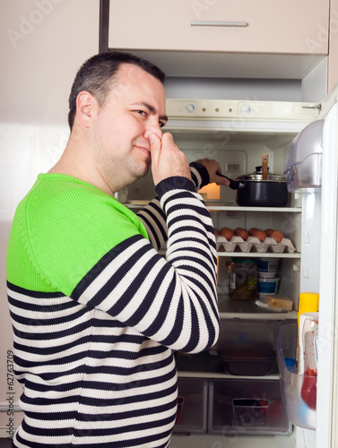 Guy looking for something in pan near fridge