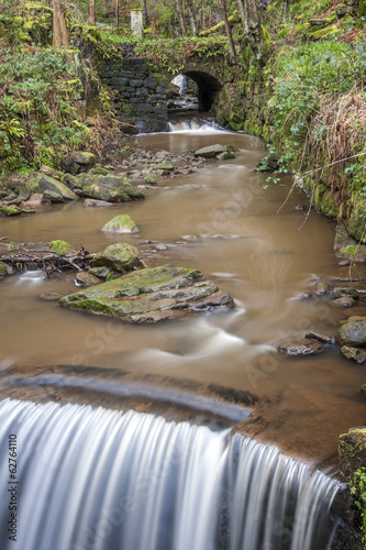 stone bridge and weir in yorkshire woodland
