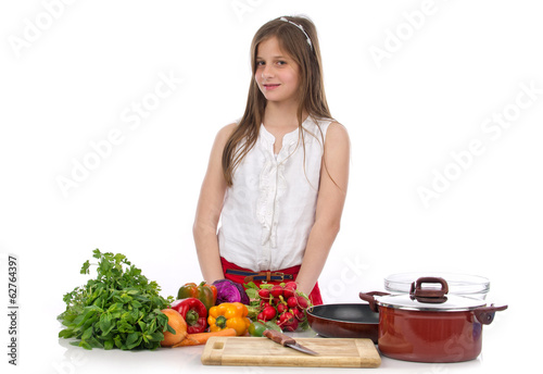 A young teenage girl preparing food isolated on white..