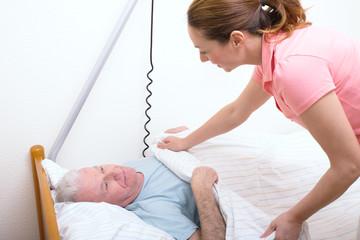 pflegerin deckt senioren zu