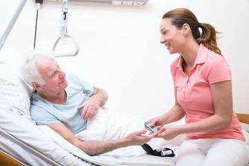Pflegerin bei der Blutzuckermessung beim Patienten