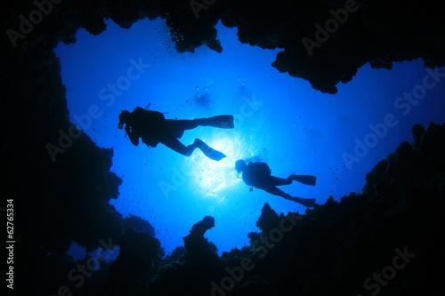 Scuba Divers swim over underwater cave - 62765334