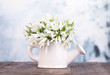 Beautiful snowdrops in vase, on table on bright background