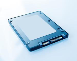 SSD disk drive in blue technological background - tilt-shift