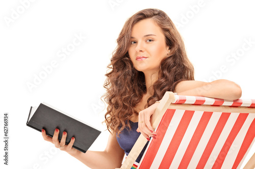 Pretty girl holding a book seated on sun lounger
