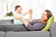 Woman lying on sofa and playing with a baby girl