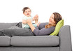 Woman lying on sofa and looking at her daughter