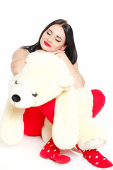 Beautiful young brunette woman holding a teddy bear