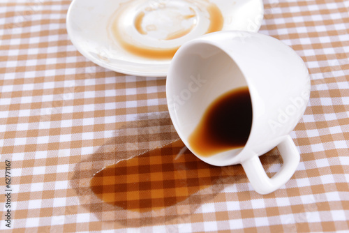 Overturned cup of coffee on table close-up