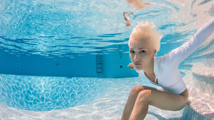 Woman wearing swimsuit underwater in swimming pool.