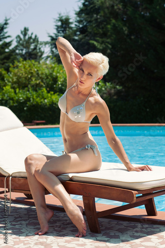 Sexy woman portrait in bikini sunbathing by swimming pool resort