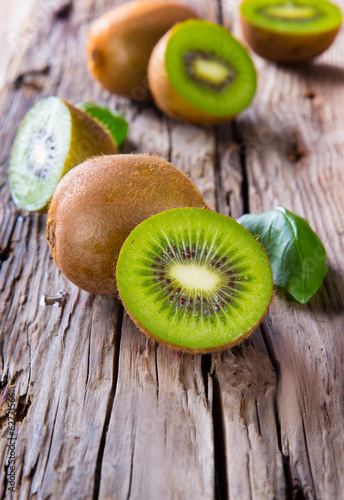 Fresh kiwi fruits on wooden table. Wooden background.
