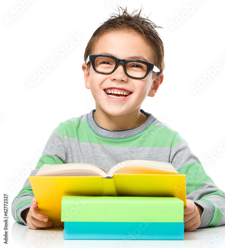 Little boy is reading a book