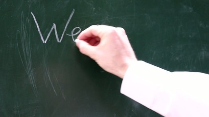 Eine Männerhand schreibt  wer weiss es auf eine Tafel