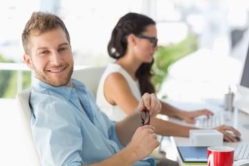 Attractive designer smiling at camera at desk