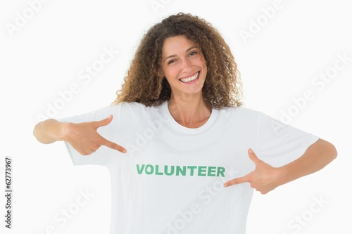 Smiling volunteer pointing to her tshirt looking at camera