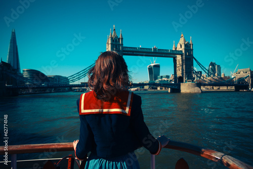Young woman on boat looking at Tower Bridge in London