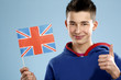 young smiling male student teenager holding a flag