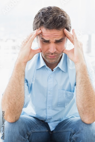 Wincing man with headache sitting on the couch