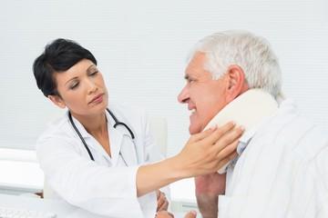 Female doctor examining a senior patients neck