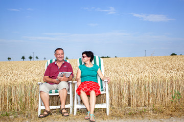 Man and woman sitting in the garden chair in front of the field