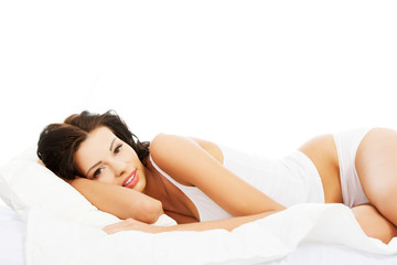 Happy sensual woman lying in bed