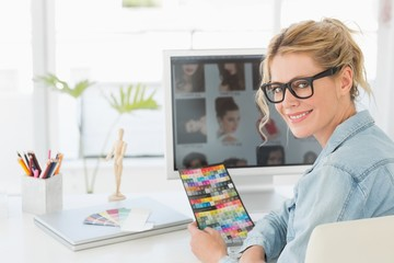 Blonde designer holding colour chart at her desk smiling at
