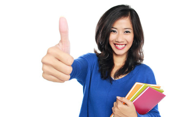 Young female student with books showing thumb up
