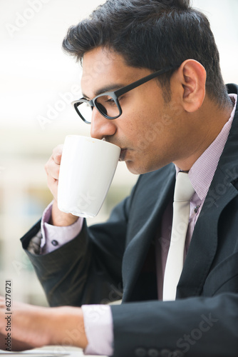 close up of young indian business man enjoying coffe during work