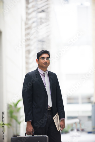 young indian business male holding suitcase