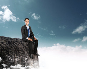 businessman sitting on the top of a high mountain