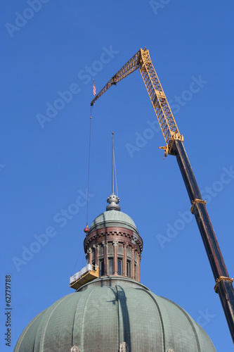 A Crane holding a lift to clean the dome of the building