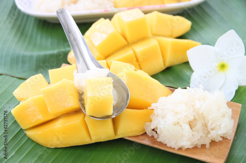 Ripe mango and sticky rice in spoon on banana leaves.