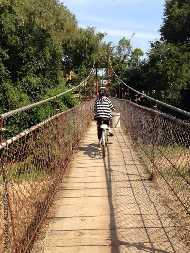 Local riding across a hanging bridge in Battambang, Cambodia