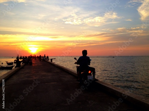 Man riding motorcycle watching dramatic sunset